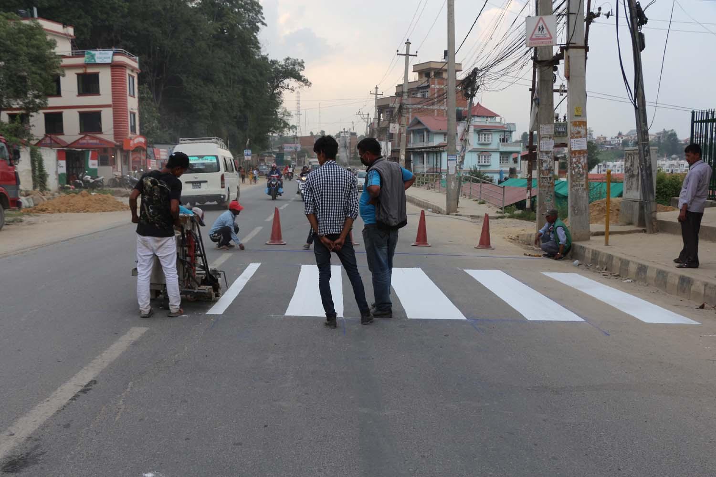 ललितपुरको लिटिल एन्जल्स स्कुल अगाडिको सडकमा जेब्रा क्रसिङ निर्माण गर्दै मजदुरहरु